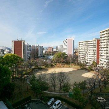 こちら、廊下側からの眺望。公園を囲むように団地の住棟が並びます。ナゴヤドームが見えるのわかりますか?