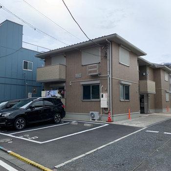 2階建てのアパート。道路沿いに駐車場があります。