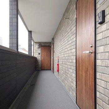 共用廊下の壁もレンガ柄。凹凸もしっかりあるこだわり…!