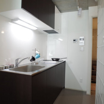 キッチンはステンレスでフラットなつくり。※写真は2階の同間取り別部屋のものです