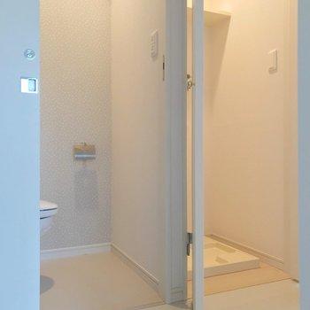 反対側にはトイレと、扉で隠せる洗濯機置場。(※写真は7階の同間取り別部屋のものです)