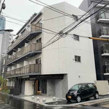 白い壁が目印、4階建てのマンションです。
