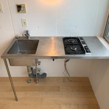 二口ガスキッチン。シンクの下に、洗濯機用の蛇口と排水のパイプがあります。