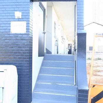 【共用部】マンション入り口。階段を上がって、さらに左の階段で2階へ。
