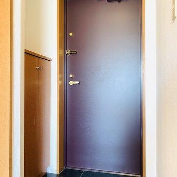 玄関はワインレッドの扉にブラックの床でシックに。