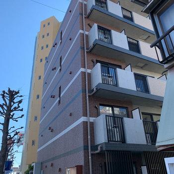 道路沿いのレンガ調のマンション。
