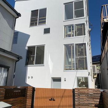 窓の多い白い建物。ゲートの木の風合いも素敵です。