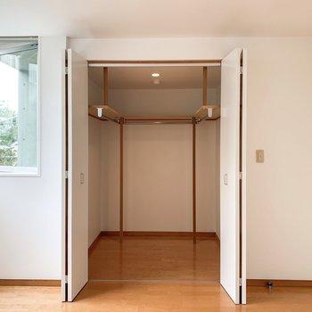 【洋室】ウォークインクローゼットがこんにちは。3面にハンガーポールが付いているので、洋服をたっぷりかけられます。