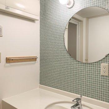 まあるい鏡、かわいらしい水色のタイル、タオルハンガーのさりげない木材......。キュンとせずにはいられません。