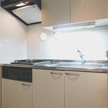 白いパネルのキッチン。手が届きやすい位置に吊り戸棚がありますね。