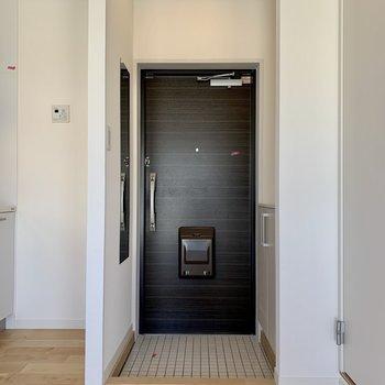 玄関は白いタイルで明るい印象。