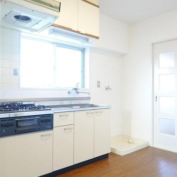 真っ白で清潔なキッチン。右手には洗濯機置場。
