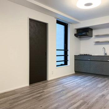 【LDK】キッチンの左に窓と、洋室への扉。