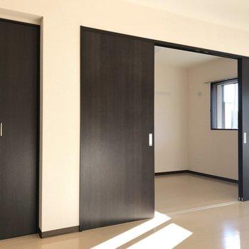 【LDK】開ければより開放感が。引き戸の横には、収納スペースも付いています。※写真は1階の反転間取り別部屋のものです