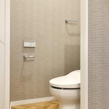そのまた隣は仕切りを隔ててトイレです。壁紙がタイル模様ですね。