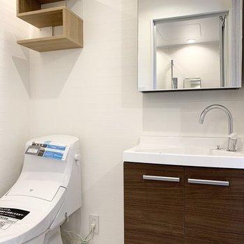 木目の洗面台とトイレ上の棚がいい。