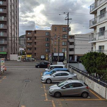 約4帖洋室からの景色。市電のある広めの道路と駐車場が見えます。