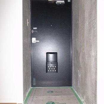 玄関はゆるっとした丸みに遊び心を感じます。ここもコンクリート! ※フラッシュを使用しています。