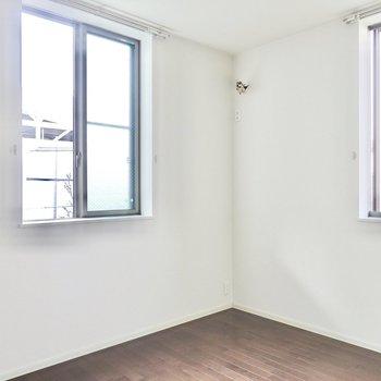 洋室は約6.1帖。二面採光で柔らかな印象。白のベッドファブリックを合わせた寝室に。