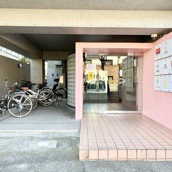 駐輪場と、ピンクなエントランス。