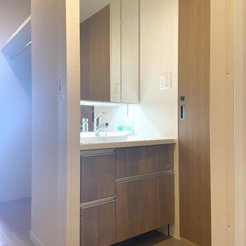 開けるとサニタリールームに!とっても鏡の大きな洗面台です。 ※写真は7階の同間取り別部屋のもの