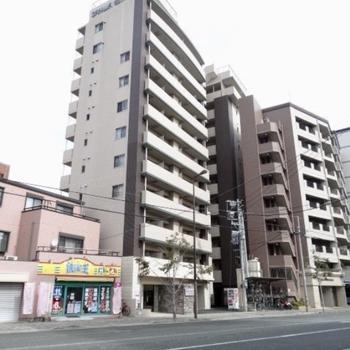 道路沿いの11階建てマンション。