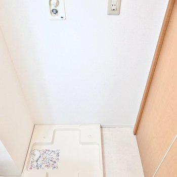 右手には洗濯機置き場。収納ケースを置けるスペースも。