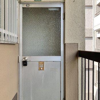 プレハブのような簡素な玄関扉とチャイムボタン。素朴さが愛らしいなぁ。