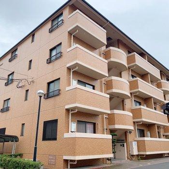 どっしりした鉄筋コンクリート造のマンション。周りは住宅街です。