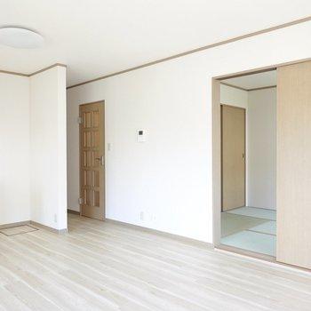 対面側を。隣には和室があり、左奥には玄関や水回り、洋室が。