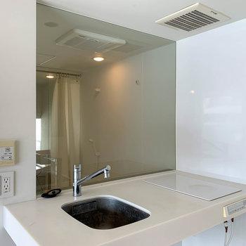 二口IHのキッチン。ガラス越しにお風呂が見えます。