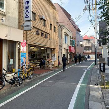 マンション前の通りです。精肉店や人気のある定食屋さんがあります。