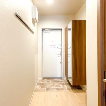 廊下の奥には玄関。壁にはフック付きのピクチャーレール、靴箱には姿見付きです。
