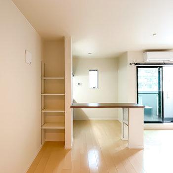 小上がりの対面にはキッチンのカウンター。サイドには収納として使える可動棚も。