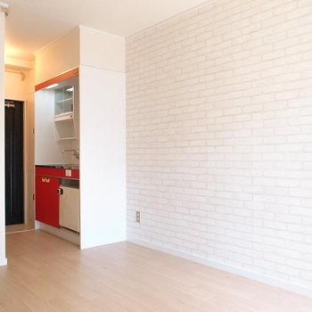 レンガ柄のアクセントクロスとキッチンの赤色で外国風のデザインです。