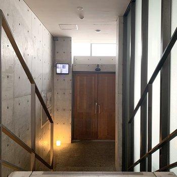 コンクリの中にここだけ木の扉が素敵なエントランス。エントランスからエレベーターへのアクセスは階段を介しますが、フラットなルートも用意されていました。