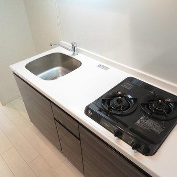 キッチンは2口コンロのシステムキッチンです(※写真は7階の反転間取り別部屋のものです)