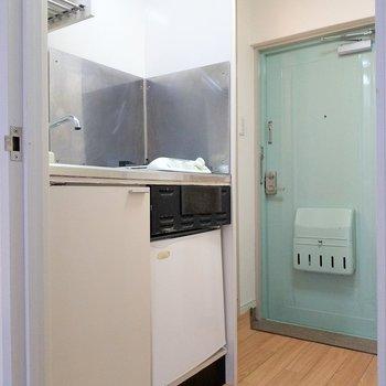 キッチン下にはミニ冷蔵庫。ミントグリーンの玄関扉がアクセント!