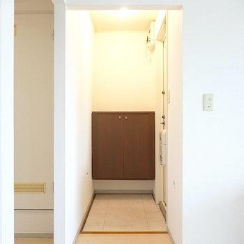 玄関はキッチンの隣。スペースの広いタタキの奥に靴箱。