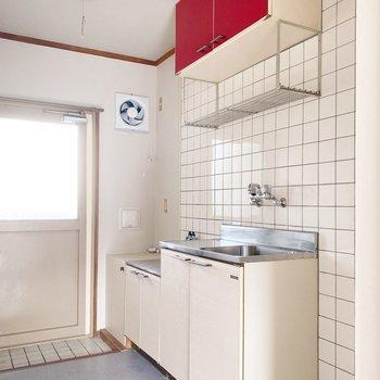 キッチン上の収納の赤色が映えてますね。