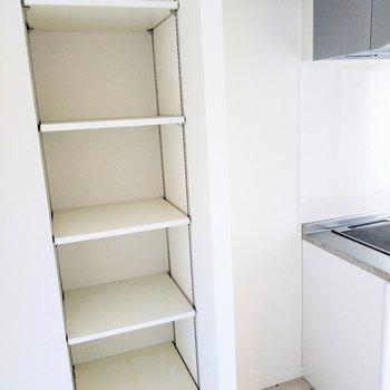 キッチン横に冷蔵庫置けそう。備え付けの棚には食器や食品をしまおう。(※写真は8階反転間取り別部屋のものです)