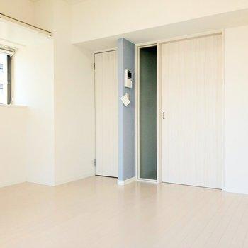 ブルーの壁が白い壁のアクセントに。天井にも棚がありますよ。左の扉を開けると…?(※写真は8階反転間取り別部屋のものです)