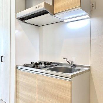 きれいな木目パネルのキッチン。※写真は2階の同間取り別部屋のものです