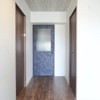 正面の黒いドアの先は廊下。右手のドアを開けると…?(※写真は5階の同間取り別部屋のものです)