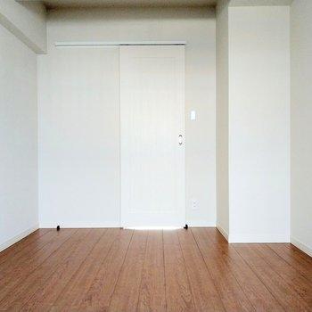 木目の床に白壁がナチュラルで素敵。正面の扉は…?