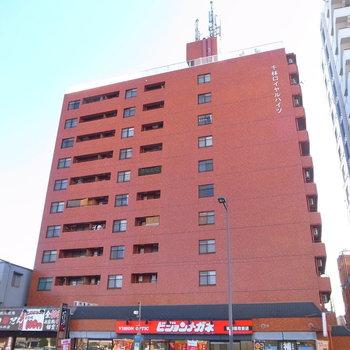 大通り沿いの、どっしりした赤レンガ風の建物です。1階にはメガネ販売店が入っています。