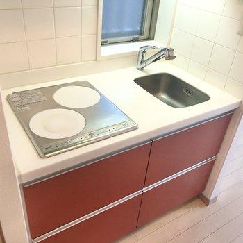 赤色が可愛らしいキッチン。小窓が付いていて換気もできます。