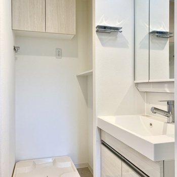 脱衣所。洗濯機置き場の右にシェルフがあります。