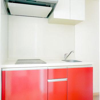 綺麗でスタイリッシュなキッチン。赤いパネルが良い差し色になっています。