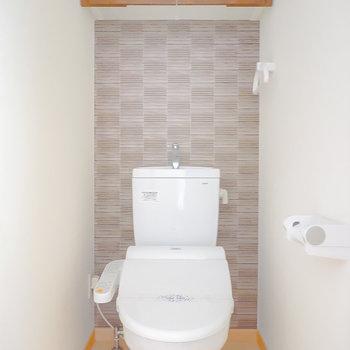 アクセントクロスの空間に、ウォシュレット付きのおトイレ。収納棚も付いています。